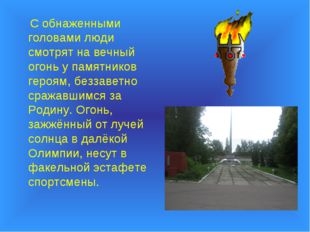 С обнаженными головами люди смотрят на вечный огонь у памятников героям, без