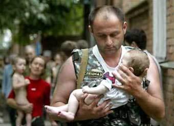 Офицер спецназа несет спасенного ребенка. Фото Reuters.