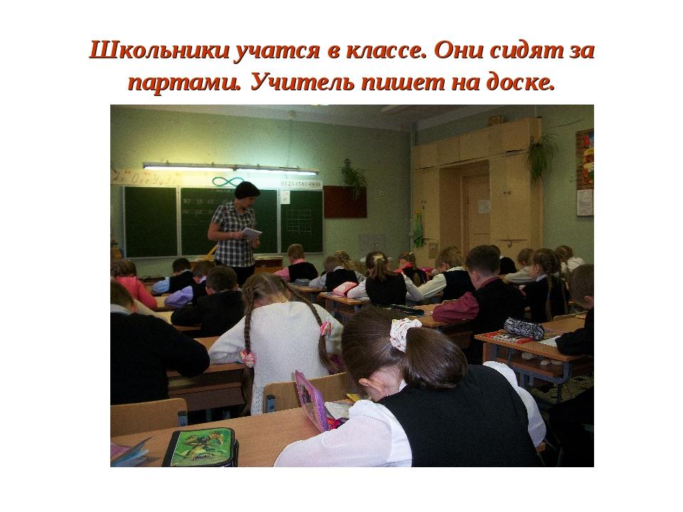 Школьники учатся в классе. Они сидят за партами. Учитель пишет на доске.